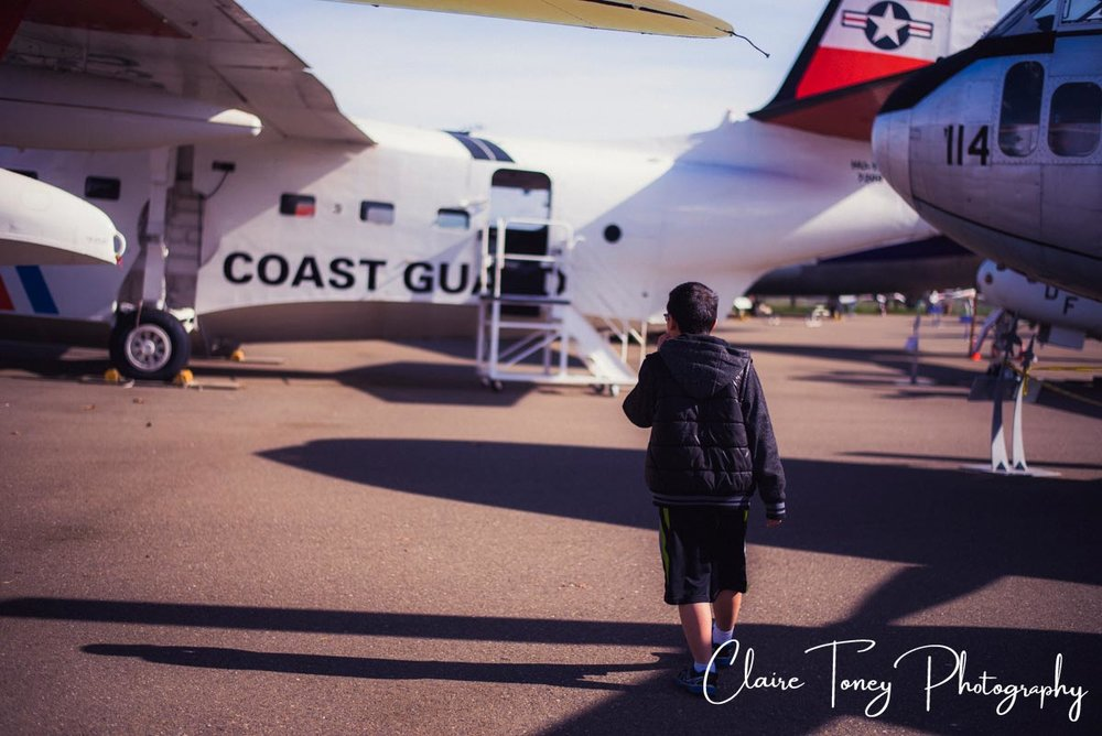 Boy walking towards a Coast Guard plane at the Aerospace Museum, Sacramento CA