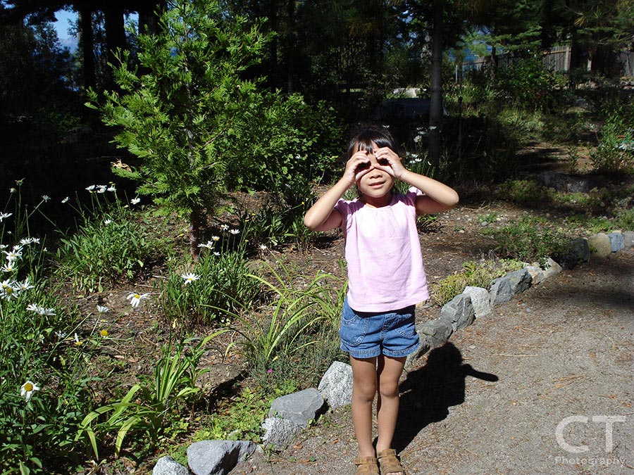 Young girl shielding her eyes from the sun with her hands cupped like sunglasses.