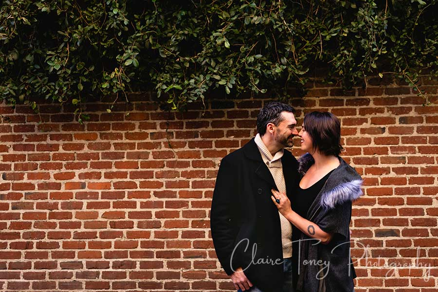 A couple looking at each other in front of a brick wall