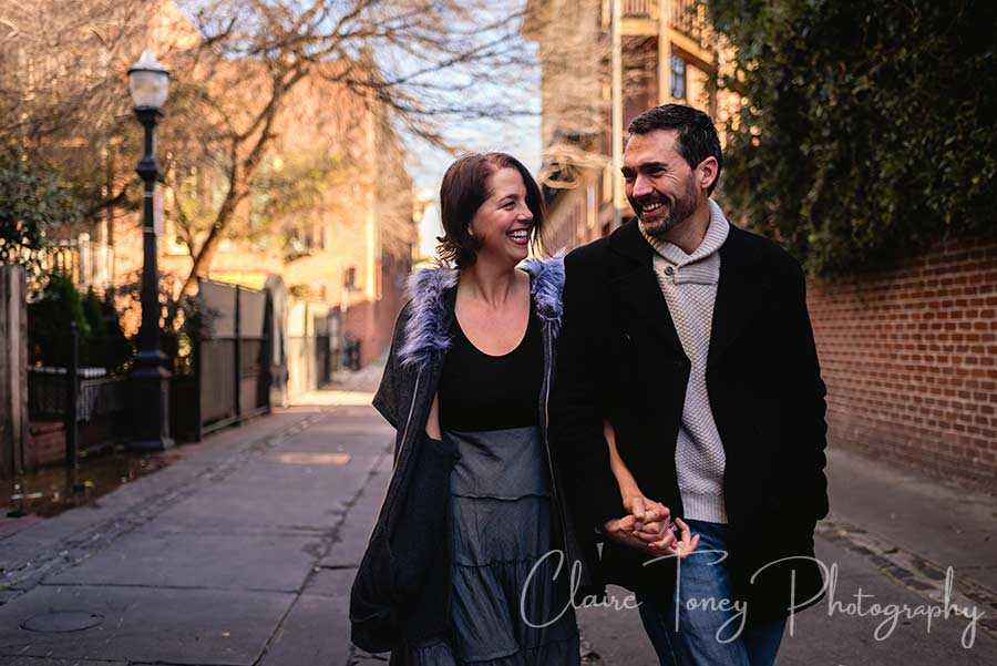 A couple laughing and walking in an alley