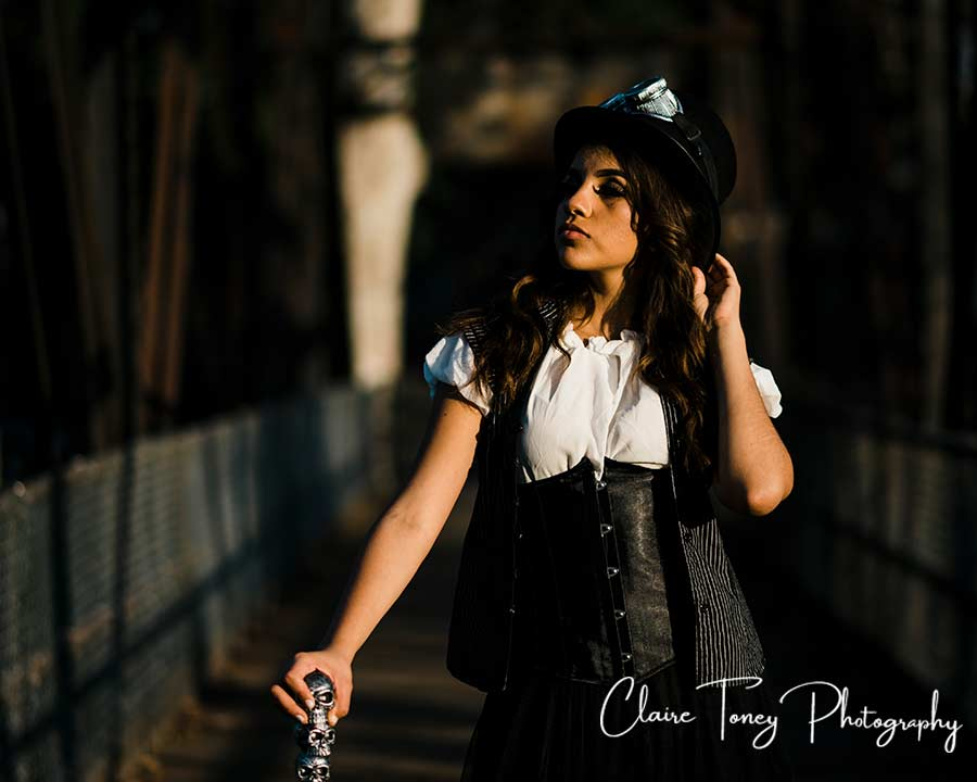 Teen on a metal bridge wearing steampunk inspired clothing