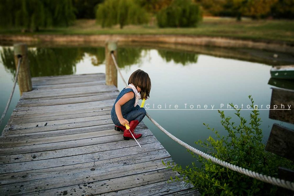 Little girl squatting on a dock by a manmade lake in Orangevale CA