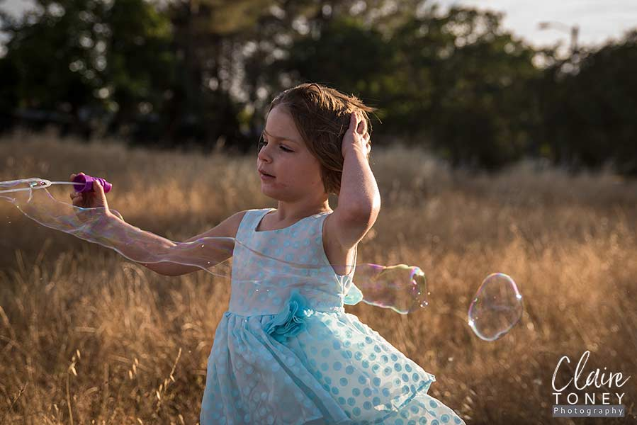 Girl playing with bubbles on a windy day, wearing a blue dress