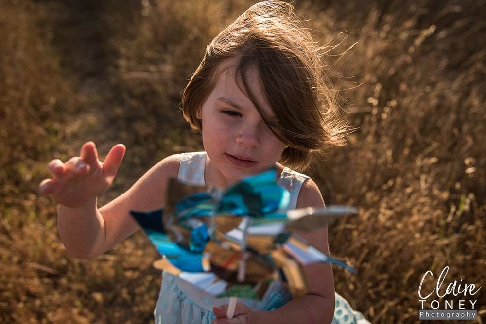 Little girl wearing a blue dress and playing a pinwheel during a windy day