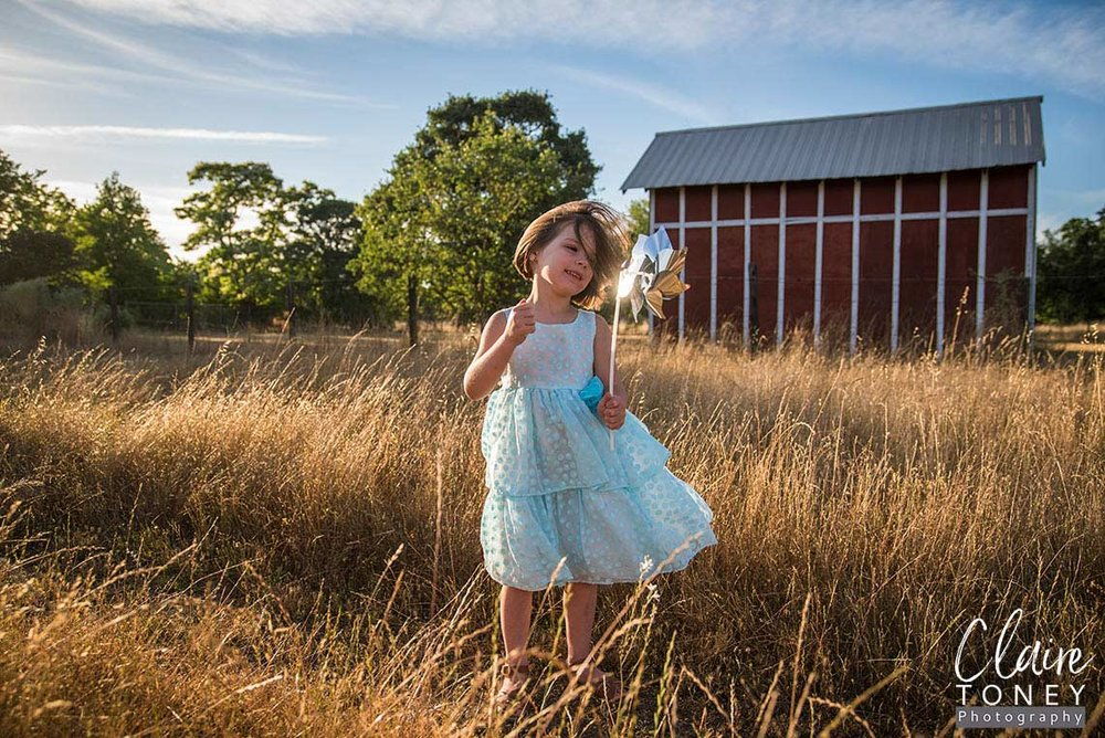 Little girl standing in front of a barn admiring a pinwheel during a windy day