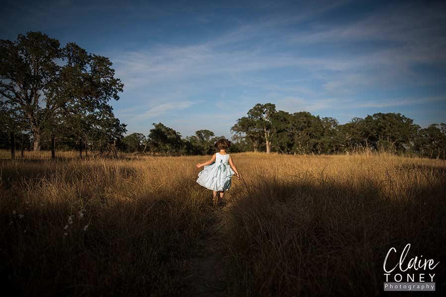 Girl running in a golden field at sunset