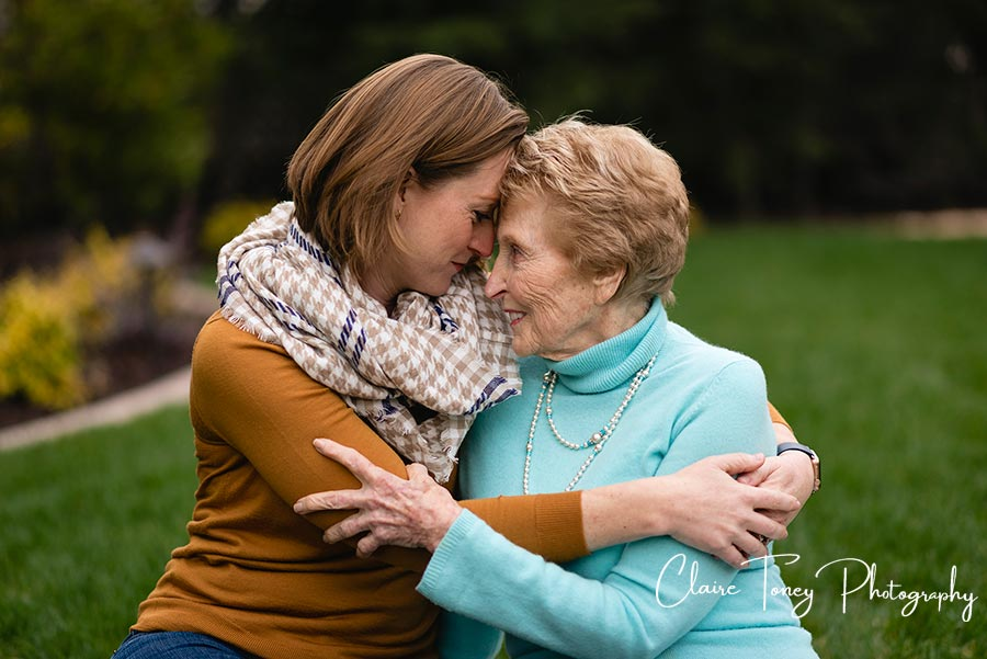 Adult granddaughter and grandmother hugging and looking at each other with their foreheads touching