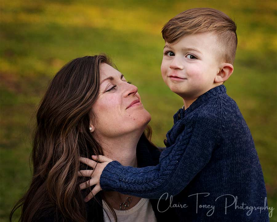 a mom looking at her son who is looking at the camera
