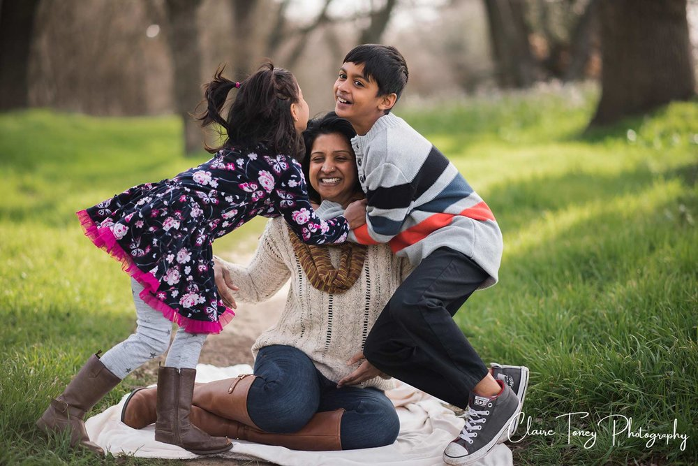 a laughing mom sitting on the ground and her children are about to land on top of her