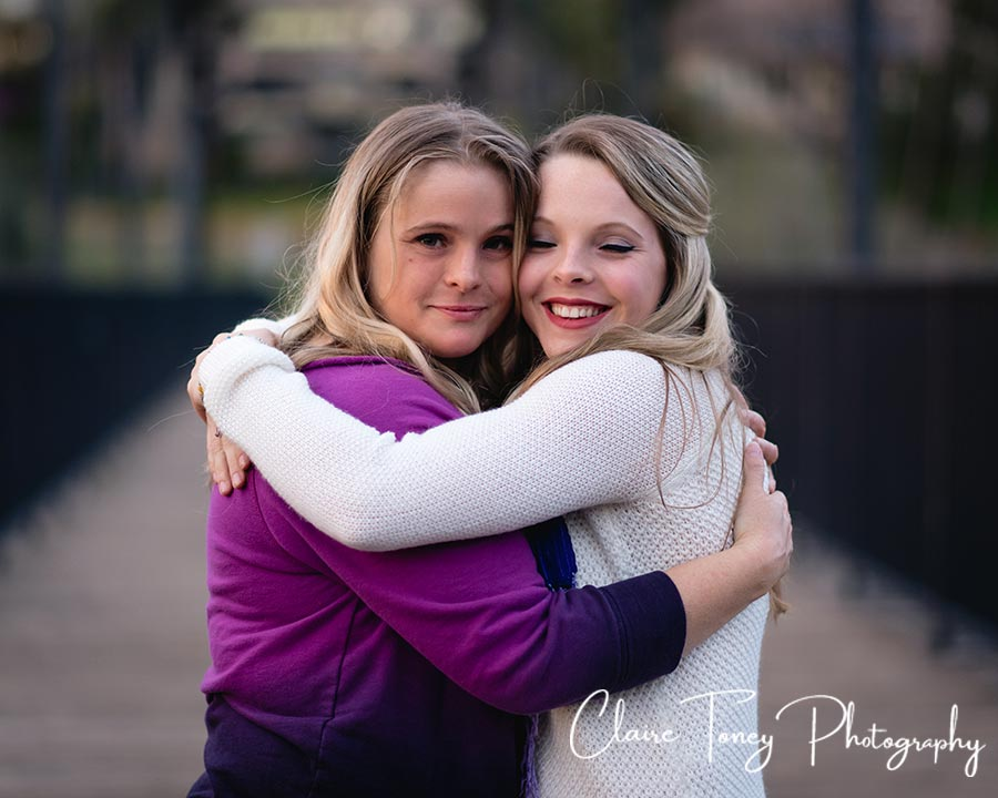 Mom and her daughter hugging on a bridge at Folsom CA