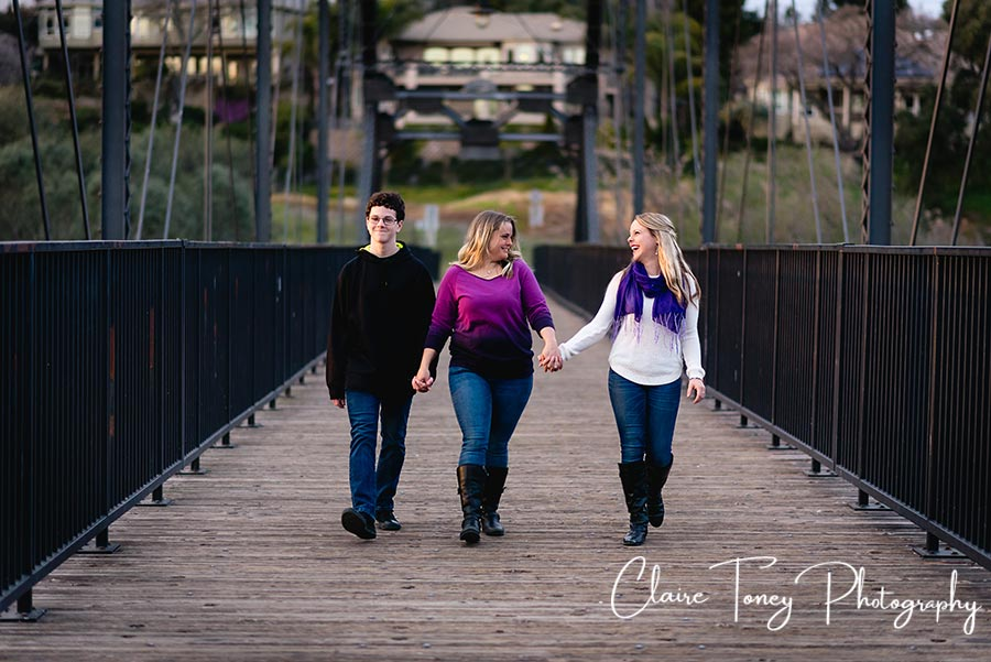 Mom and her two older children walking and laughing on a pedestrian bridge in Folsom CA
