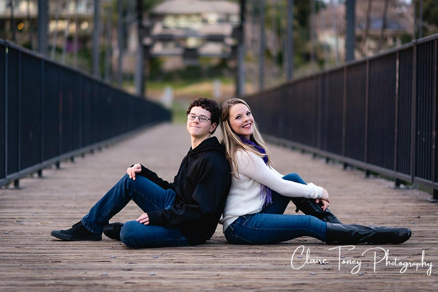 Brother and sister sitting back to back on a bridge