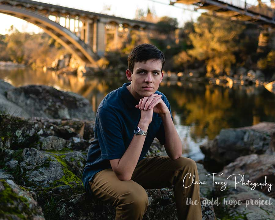 Young man sitting on rocks in front of a bridge during sunset, Folsom CA