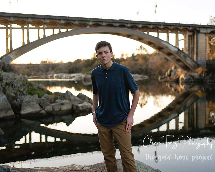 Young man standing in front of a bridge in Folsom California