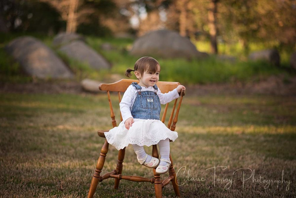 Little girl sitting on a wooden chair in a Folsom CA park