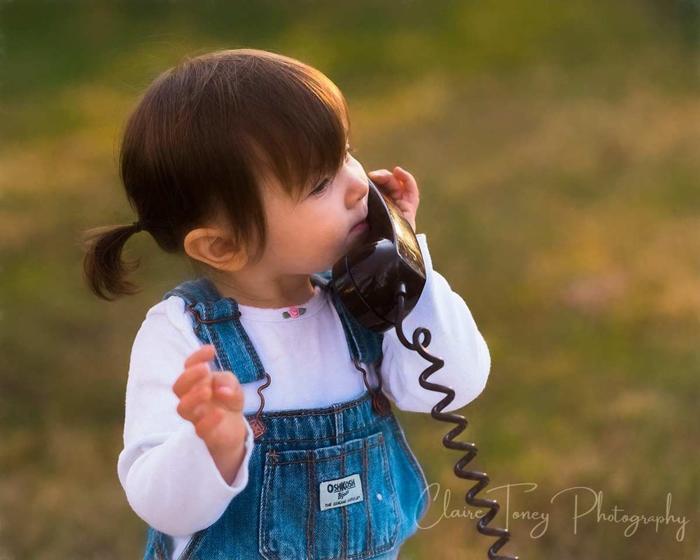 Little girl speaking on a brown old fashioned phone