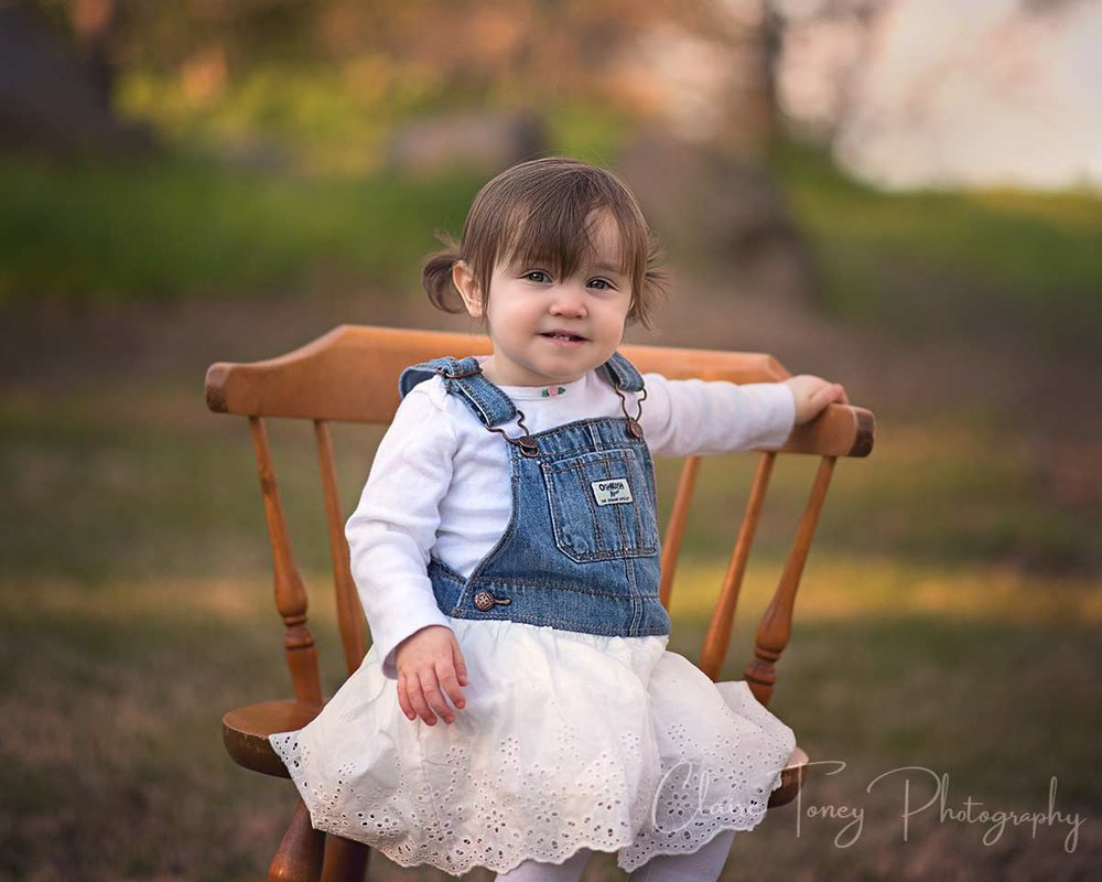 little girl with bright eyes sitting on a wooden chair