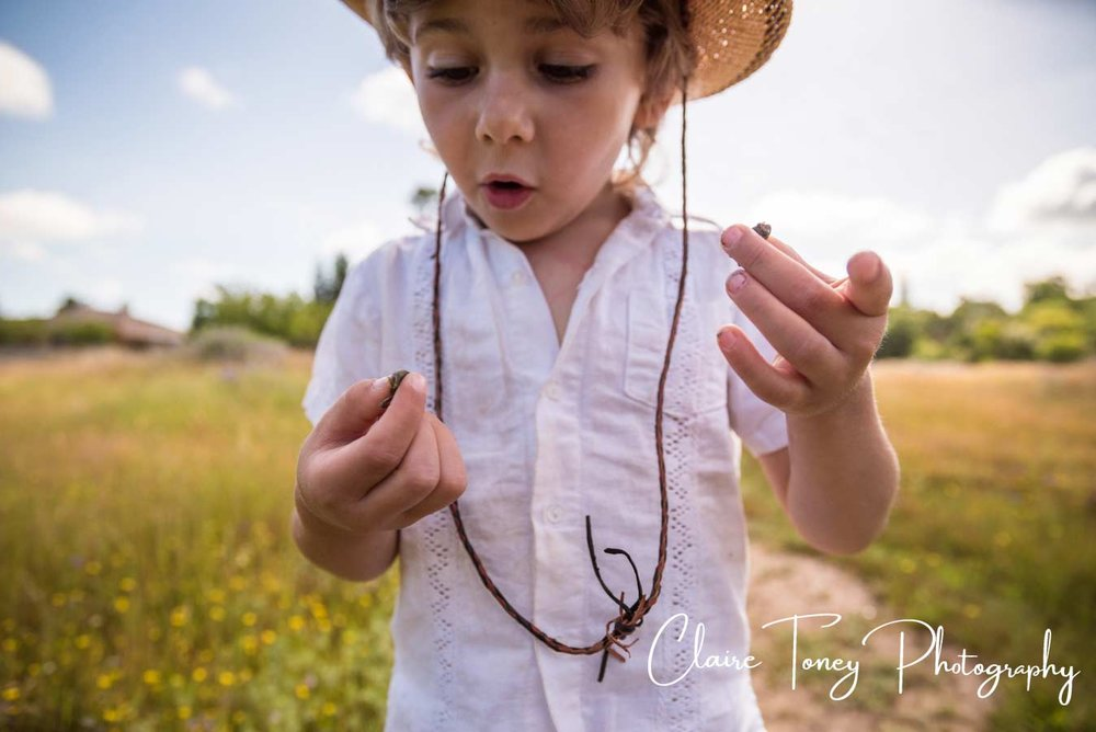 little boy in a white shirt looking at tiny frogs that he is holding in his fingers
