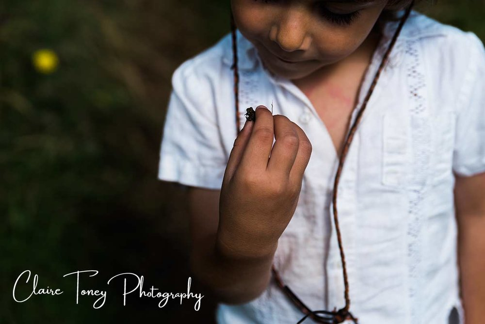 boy in white shirt looking at a tiny frog in his fingers