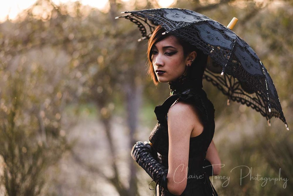 Teen girl holding a black parasol and wearing a black dress and black gloves