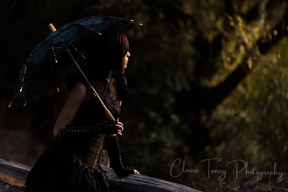 Teen girl holding a black parasol leaning against a wooden rail and facing the sunset