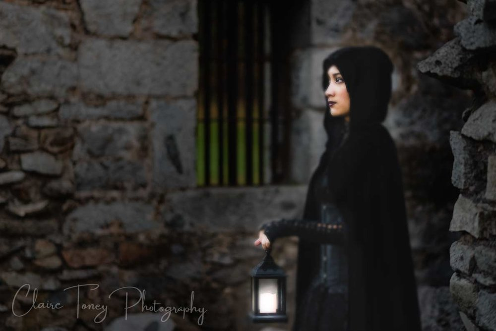 Teen girl in a black cape holding a lantern