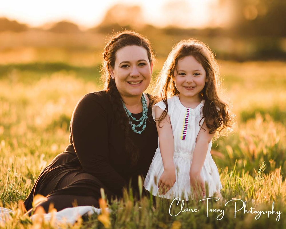 Young and her mom sitting on a field at sunset