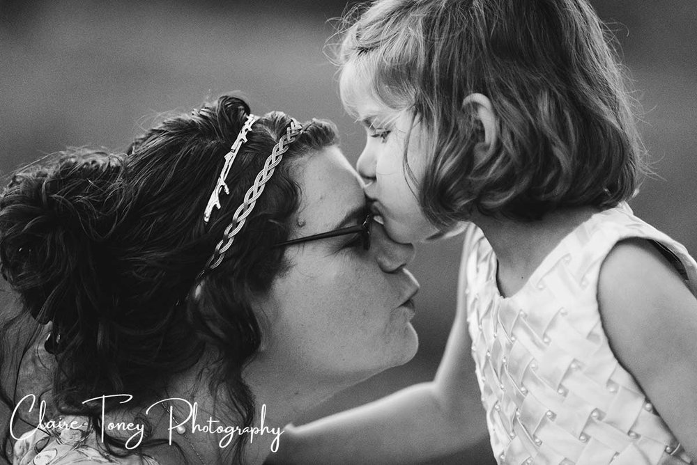 Young girl kissing her mother, who is wearing glasses, on the forehead