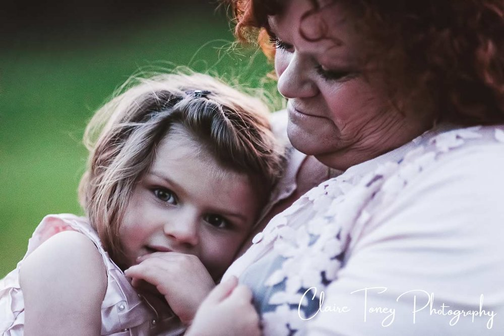 Grandmother looking at her granddaughter who is sitting on her lap and looking at the camera