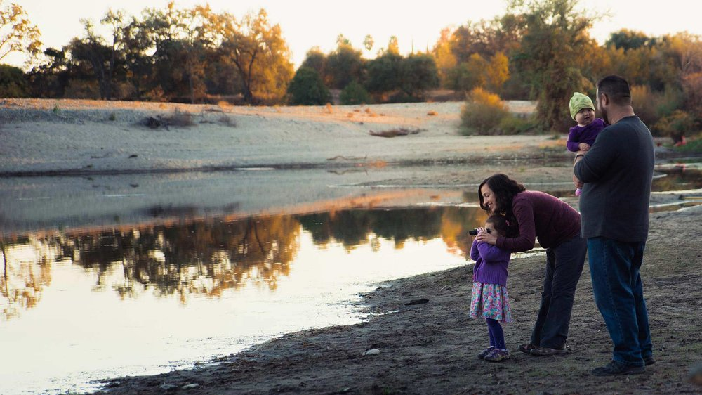 Mom helping daughter look through binoculars and dad is holding infant daughter