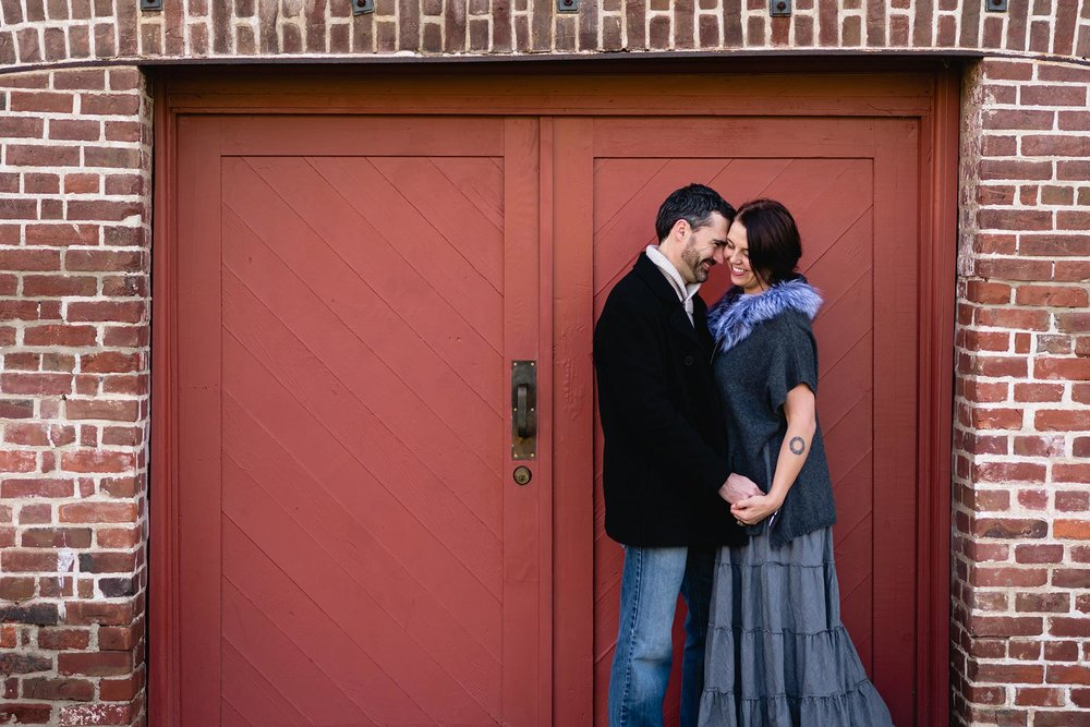 Two people cuddling in front of a red door in Old Sacramento California