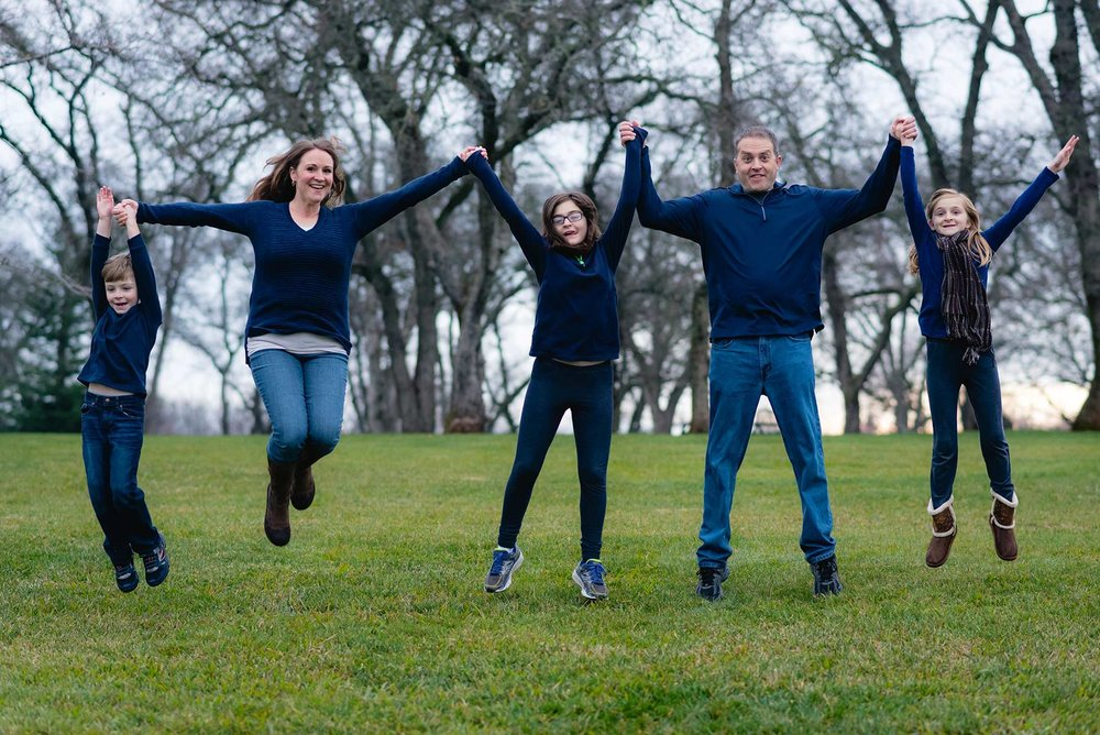 A family of 5 jumping at a park