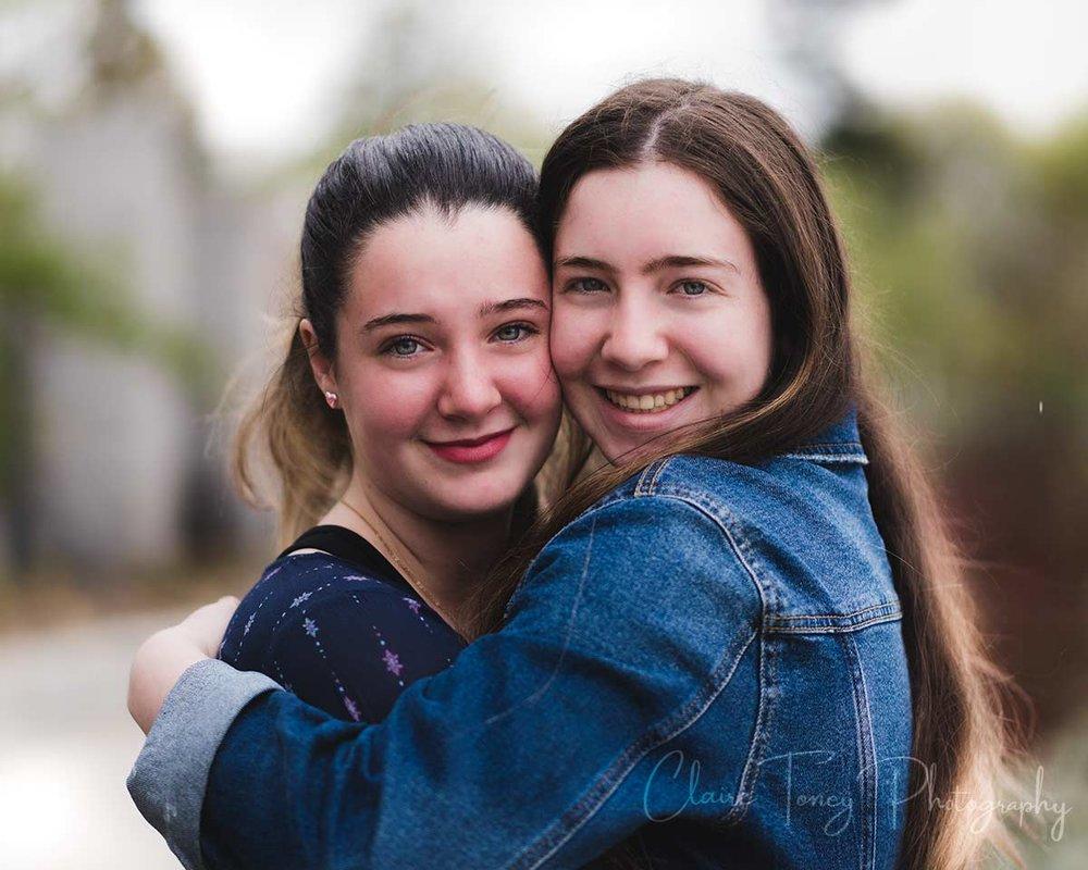 Two teenage sisters hugging in Roseville CA
