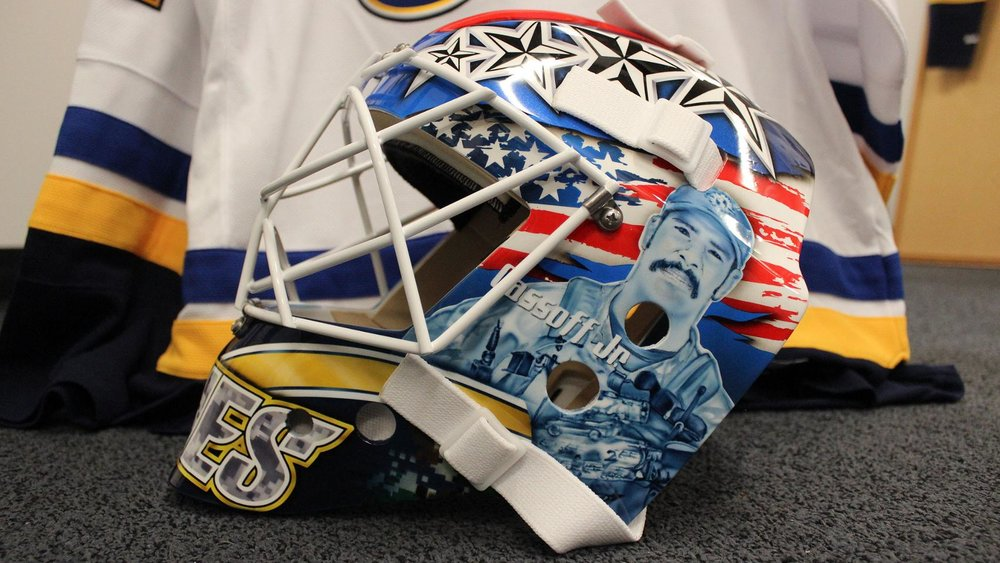 Jake Allen Military Tribute Mask - On November 11th 2017, Jake Allen will be wearing this special military tribute mask that will be raffled off after the game to help raise money for troops and their families. By combining the great colors of the United States flag, tributes to important veterans, and the St. Louis Blues logo in camo coloring, this mask will look incredible on the ice, while also helping contribute to an important cause.