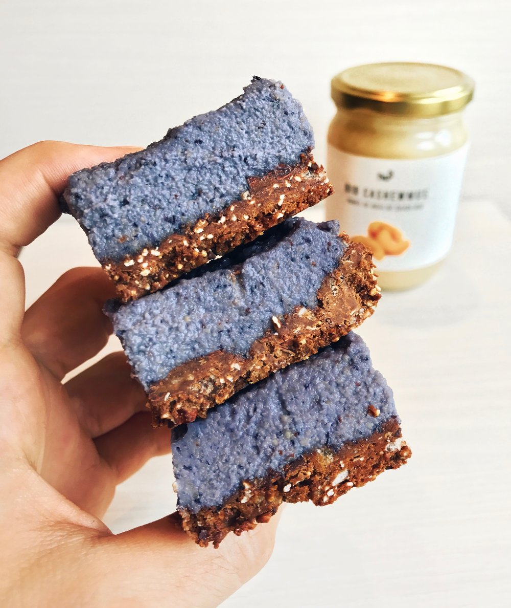 Blueberry Raw Cheesecake Bars - For the crust:- 300g of @squareorganicscrisp bars (you can also use any type of granola for it)- 1/3 cup coconut oil.Give it a whirl in your blender and spread on a parchment paper.For the creamy top:- 1 + 1/2 cups of soaked cashews (or @nu3_frcashew butter)+ 1/3 cup coconut oil+ 1/2 @driscollsberryblueberries+ 1/3 cup honey or maple syrup+ 1 lemon juiceBlend all the ingredients together until smooth, layer on top of the crust and place in the freezer for 3h. Unfreeze for 10min before eating and enjoy!