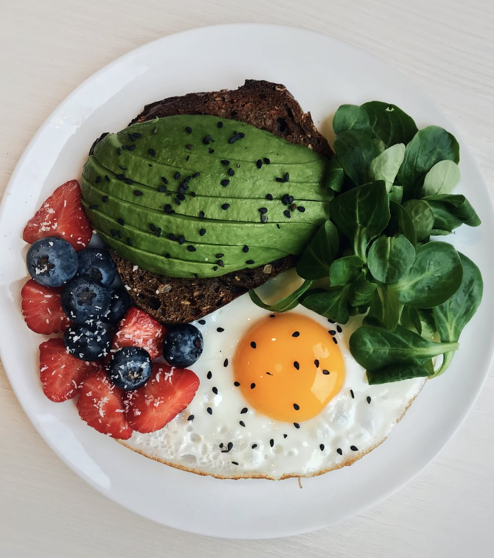 Fried Egg, Avocado Toast & Berries - Toasted nordic bread topped with @naturalia_magasins_bio avocado slices + black sesame seeds + fried egg cooking in @chosenfoods avocado oil + @florette_france salad leaves + strawberries + @driscollsberry blueberries + @vahinedesserts coconut powder