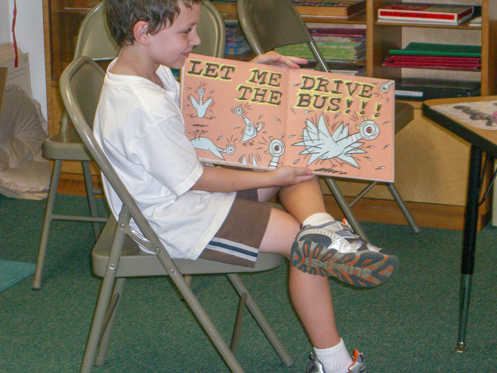 """Rader reads aloud from Mo Willems' """"Don't Let the Pigeon Drive the Bus"""" in his Montessori classroom"""