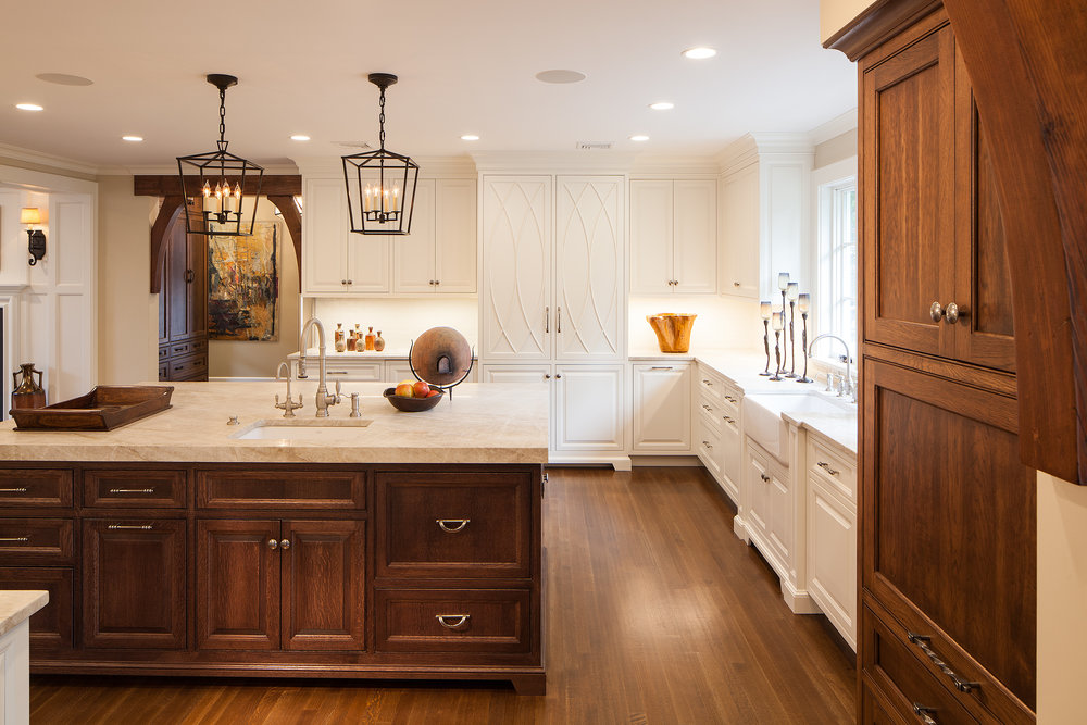 After: Kitchen with handsome natural stained wood island and white inset cabinets surrounding the perimeter.