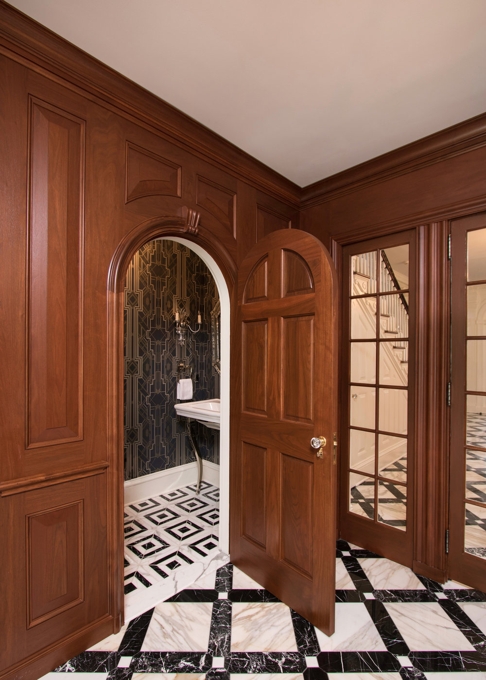 Powder room -- Relocated and refined.  Custom marble tile pattern on the floors,  wall paper and sconces re-purposed and refinished adorn the walls.