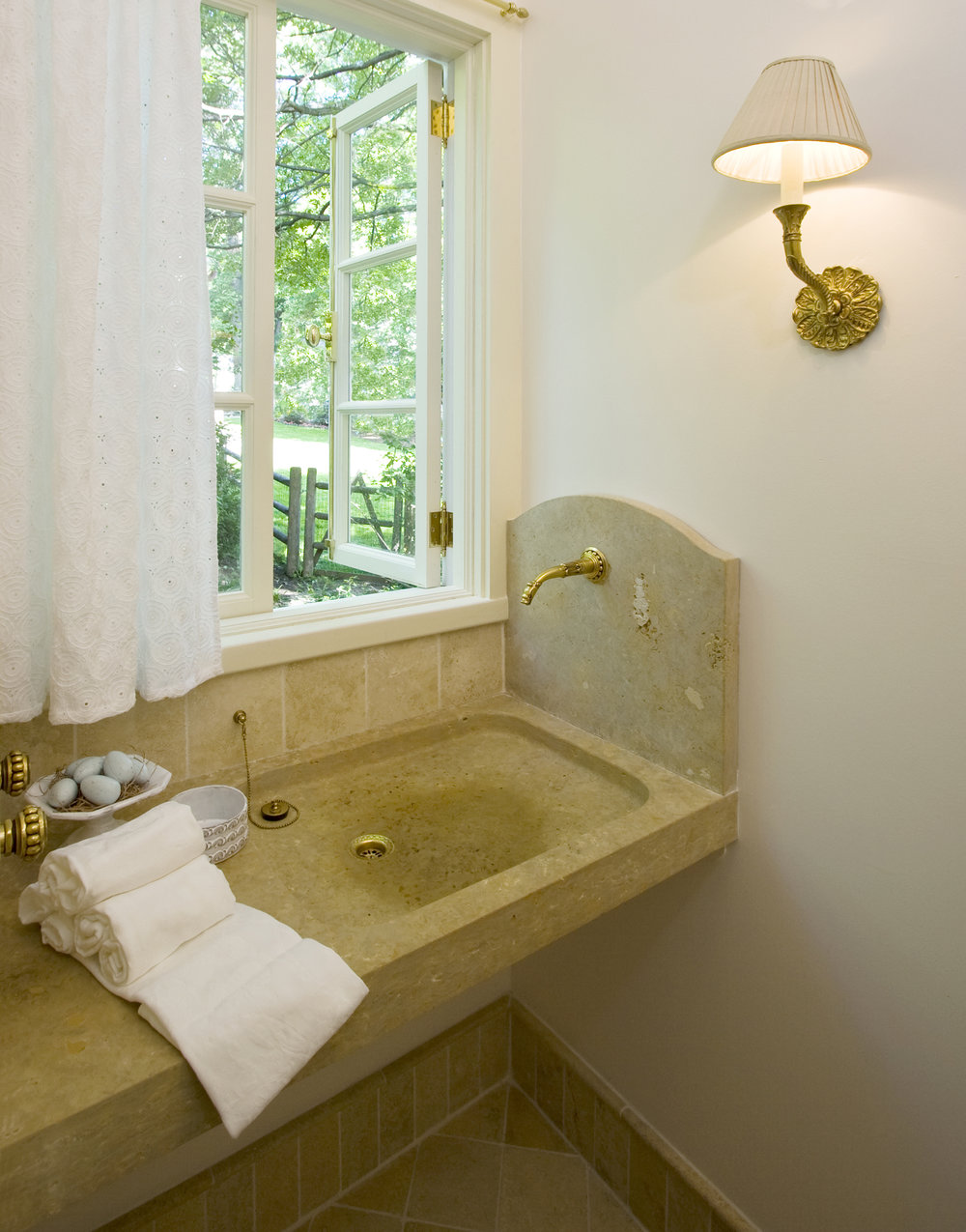 "The Powder Room is truly special.  A carved custom limestone sink was designed and built for the client and features a unique wall-mounted faucet.  Limestone tile floors and baseboard echo dreams of Roman holidays. Viva l'Italia!  ""...heart set on a stone sink like ones she had seen in European farmhouses, but was dismayed by the high price of such items. Thanks to Marvin Clawson, we got a custom-made sink made of native limestone at a fraction of the cost."" --JSP + JNC"