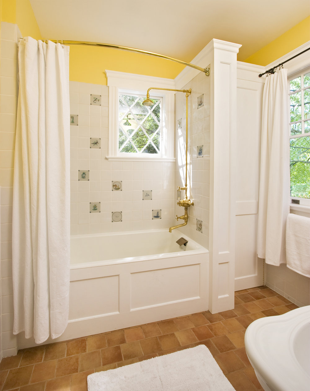 The renovated third floor bathroom features exposed plumbing, a window original to the home and Hand Painted Delft Ceramic Tiles  as well as custom millwork and terra cotta tile floors with radiant heat.