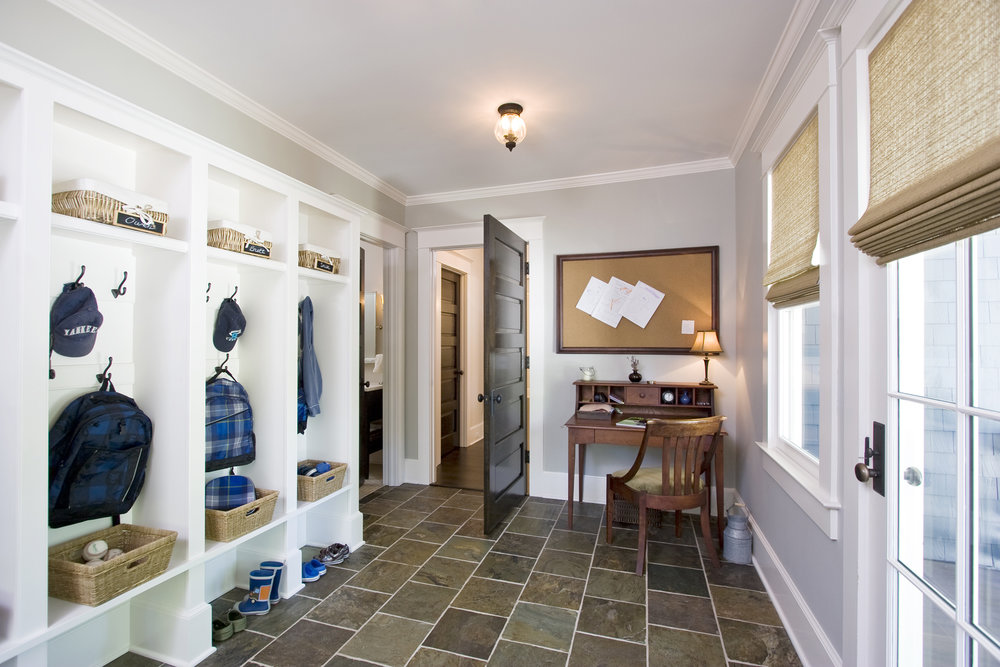 Mud room: a must-have space to keep this family of six organized!  It also has a gracious powder room too. Two large storage closets for off-season coats and boots. Desk and bulletin board keep everyone organized.