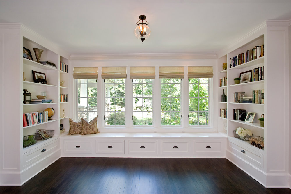 Library: Enlarging the existing opening to flood the space with more natural light while increasing storage with a custom built-in window seat and bookcases has made this area a lovely place to read or just hang out.