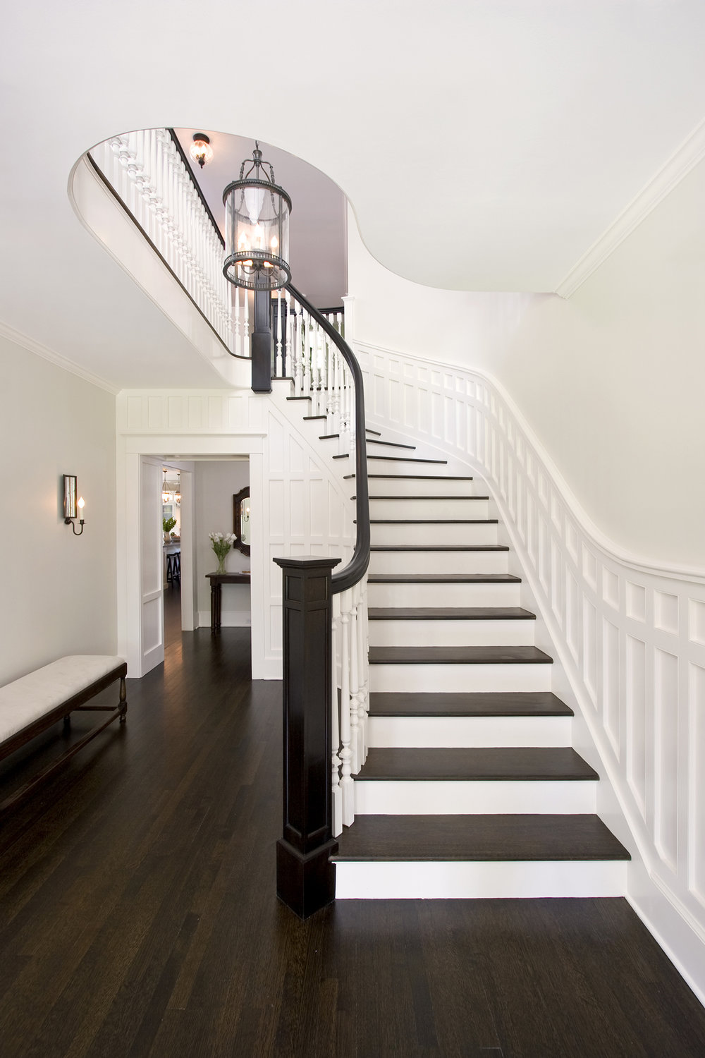 Entry Hall Stair featuring dark wood floors and white paneled wainscot.