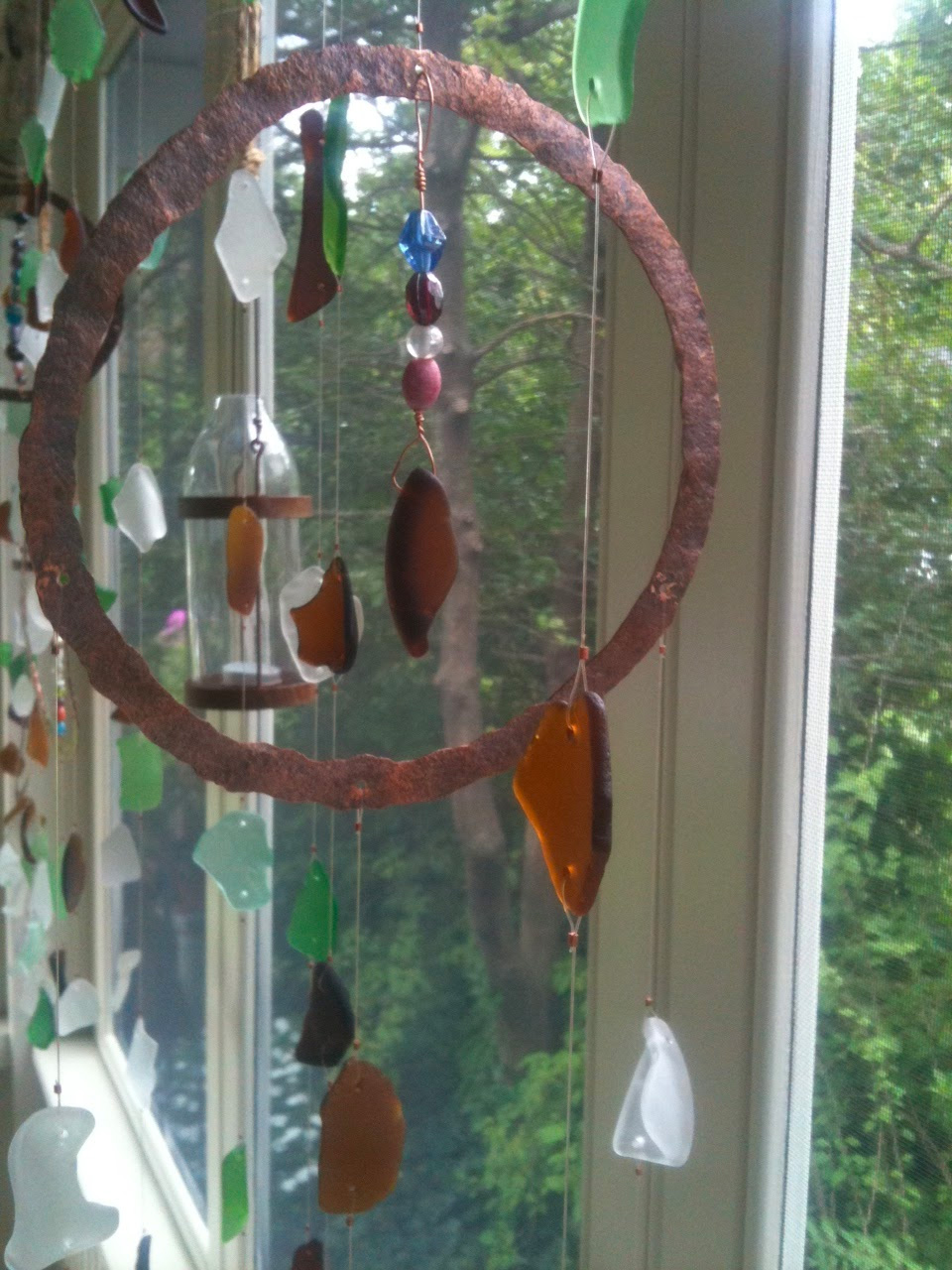 Wimsical wind chimes and a cool drink complete the mood on a hot summer day. Wind chime by Krista McCaffery—Seaglassbeach Trinkets & Treasures