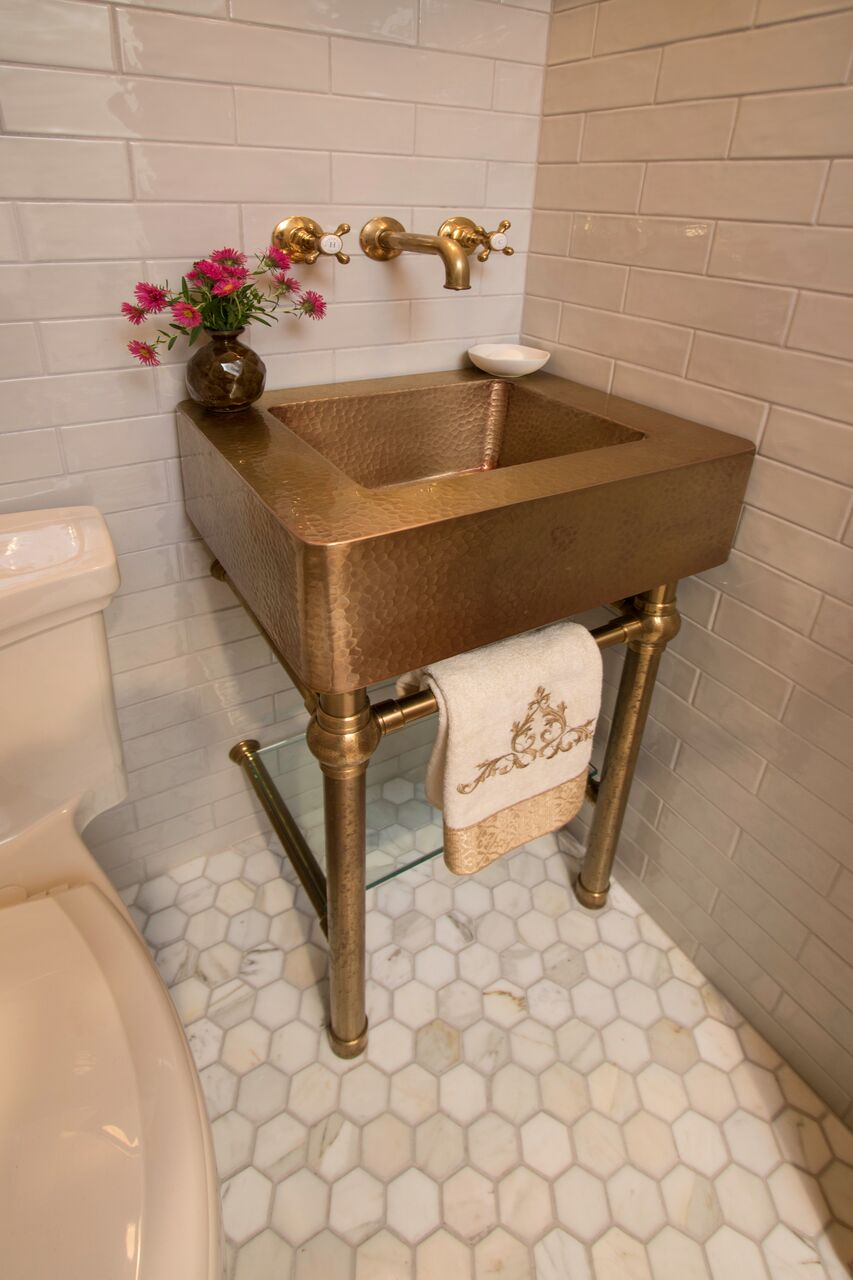 Powder room sink is an un- lacquered brass From Anew Kitchen and Bath. Faucet by Water Works Toto Toilet, and marble hex floor from Short Hills Marble and Tile.