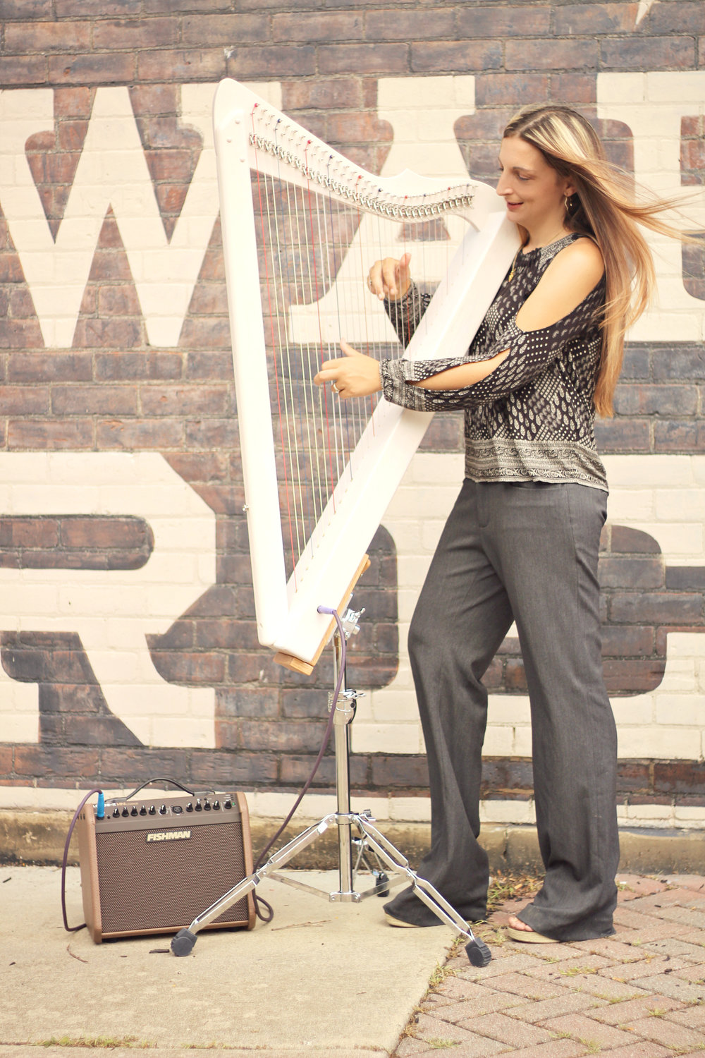 Ashley with a Grand Harpsicle® Harp in the Grand Standing Stand. She also is using the Fishman Loudbox Mini Charge Amp and an Asterope Hi Def Cable.