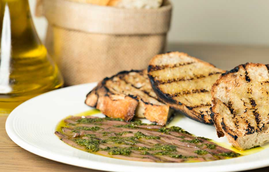 "Italian anchovies fillets, traditional ""salsa verde"", butter & grilled sourdough bread -"