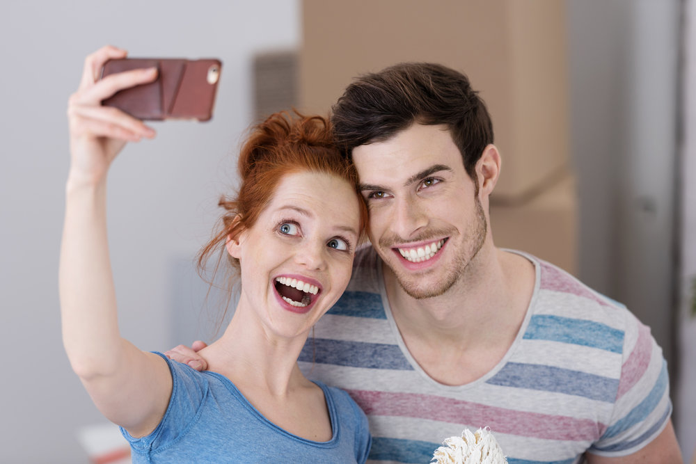 Attractive young couple with straight teeth taking a selfie and smiling after finishing In-line brace treatment