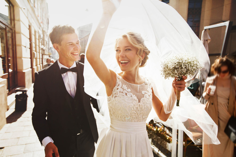 Young couple smiling on their wedding day and lady enjoying beautiful straight teeth after SmileTRU braces